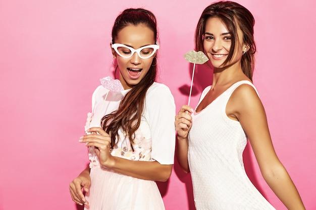 Zwei überraschte lustige lächelnde frauen in den papiergläsern und in den großen lippen auf stock. smart und beauty-konzept. frohe junge models bereit für die party. frauen getrennt auf rosafarbener wand. positive frau