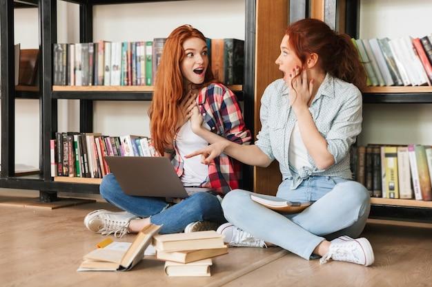 Zwei überraschte mädchen im teenageralter sitzen auf einem boden