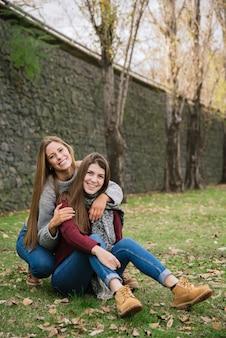 Zwei umarmende junge frauen, die im park sitzen