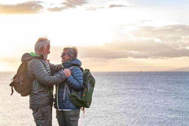 Zwei unbeschwerte ältere menschen mit rucksäcken schauen sich in die augen und genießen das wintermeer. ein schönes älteres paar, das auf der klippe mit horizont über dem wasser und sonnenuntergang steht