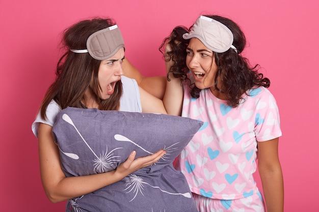 Zwei verärgerte mädchen kämpfen, während sie pyjamas und augenbinden tragen