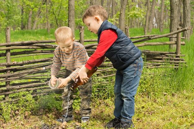 Zwei verantwortungsbewusste kleine jungs, die ein feuer löschen