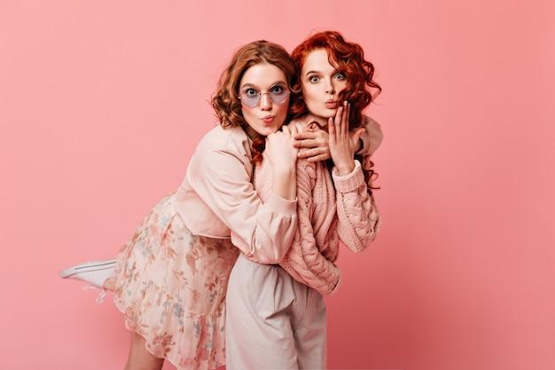 Zwei verblüffte kaukasische damen, die kamera betrachten. beste freunde, die auf rosa hintergrund umarmen.