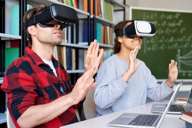 Zwei verblüffte klassenkameraden in vr-brillen, die im unterricht erstaunliche dinge in der virtuellen welt berühren