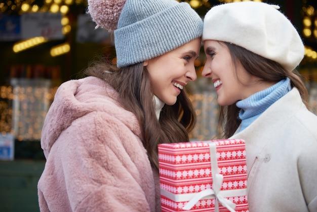 Zwei verliebte frauen, die ein weihnachtsgeschenk halten