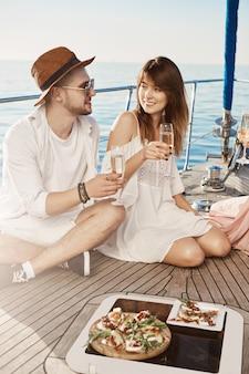 Zwei verliebte junge leute essen zu mittag und trinken champagner, während sie auf dem boden der yacht sitzen und über etwas diskutieren. enge freunde sprechen über die schrecklichsten daten, die sie hatten.