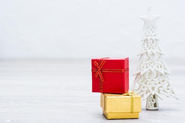 Zwei verpackte geschenke in den kästen und in weihnachtsweißem baum auf grauem hölzernem hintergrund. kopieren sie platz