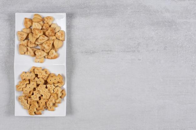 Zwei verschiedene arten von crackern auf weißem teller.