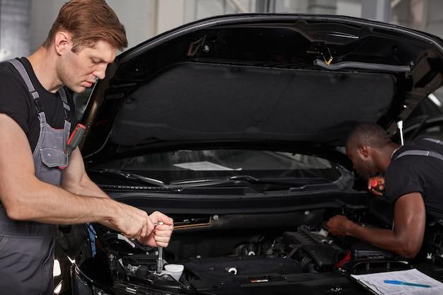 Zwei verschiedene automechaniker arbeiten bei der untersuchung des automotors zusammen