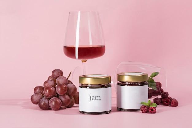 Zwei verschiedene himbeer- und traubenmarmeladen in gläsern mit einem glas wein auf rosa