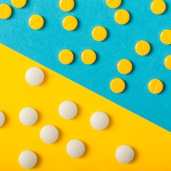 Zwei verschiedene pillen über dem gelben und blauen hintergrund