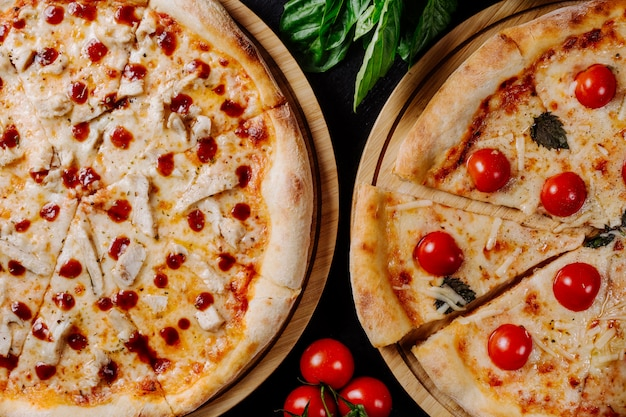 Zwei verschiedene pizzen mit kirschtomaten und peperoni.
