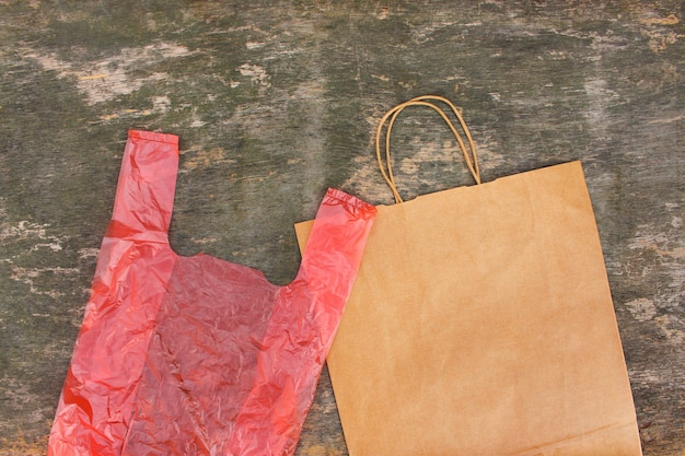 Zwei verschiedene säcke papier und polyethylen auf einem alten hölzernen hintergrund. draufsicht. flach liegen.