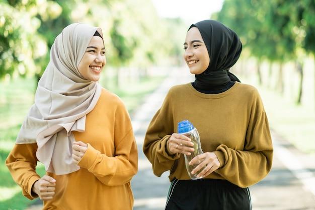 Zwei verschleierte mädchen treiben gemeinsam sport im freien, während sie sich unterhalten, und genießen es, auf dem parkfeld wasser mit einer flasche zu trinken