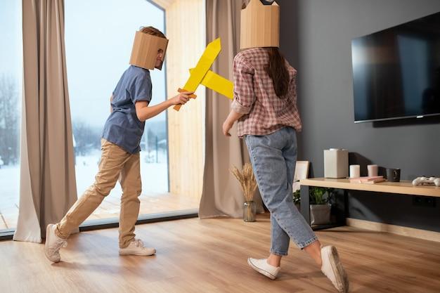 Zwei verspielte geschwister in freizeitkleidung und papphelmen kämpfen mit spielzeugschwertern gegen ein großes fenster mit beigen vorhängen im wohnzimmer