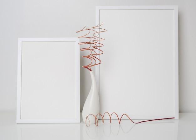Zwei verspottete weiße holzplakatrahmendekor mit getrockneten zweigenblättern in moderner weißer vase auf weißem tisch- und wandhintergrund