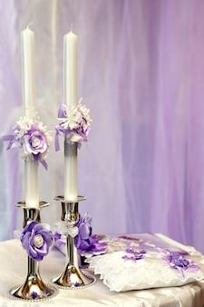 Zwei verzierte hochzeitskerzen schön auf dem tisch. festliche artikel für hochzeiten und zeremonien
