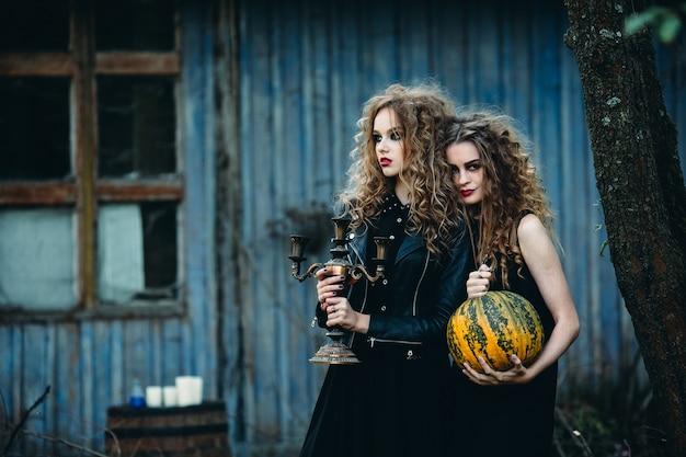 Zwei vintage-frauen als hexen, die am vorabend von halloween vor einem verlassenen haus posieren