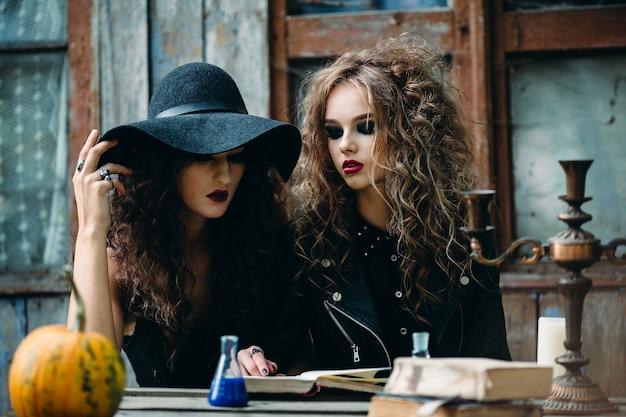Zwei vintage-hexen, die am vorabend von halloween an einem verlassenen ort am tisch sitzen