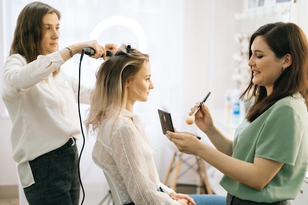 Zwei visagisten tragen der braut in der umkleidekabine haare und make-up auf