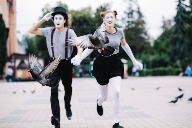 Zwei vögel, die vor laufenden pantomimepaaren auf pflasterung fliegen