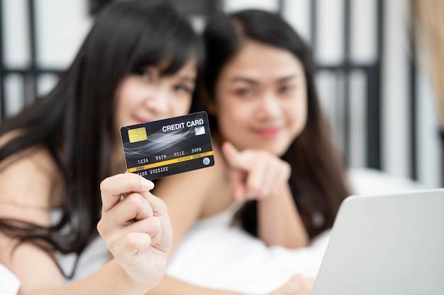Zwei von glücklichen asiatischen jungen freundinnen, die das internet für online-einkäufe auf einem laptop surfen und kreditkarte halten