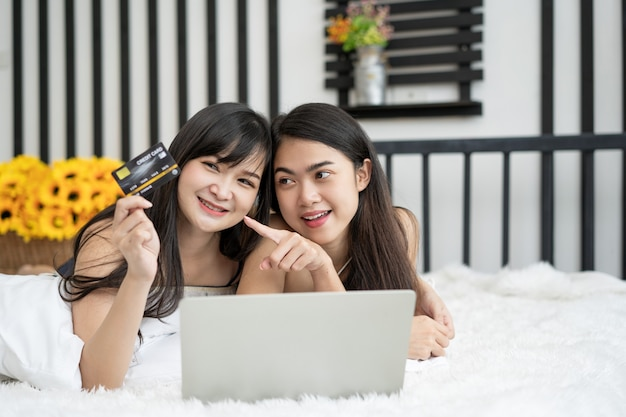 Zwei von glücklichen asiatischen jungen freundinnen, die im internet für online-einkäufe auf einem laptop surfen und kreditkarte halten