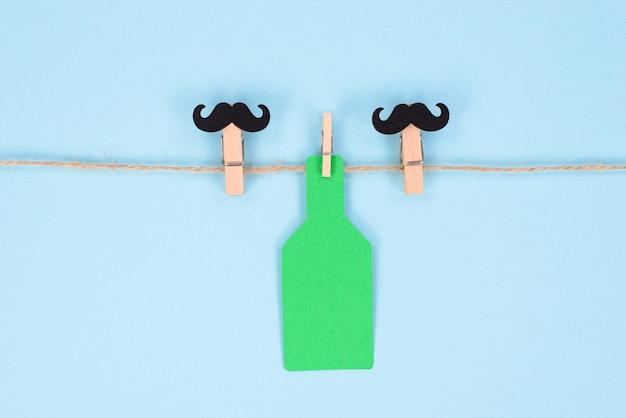 Zwei wäscheklammern mit schnurrbart und großer grüner farbflasche isolierten pastellhintergrund