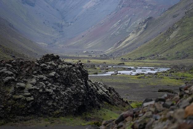 Zwei wanderer, die durch die mit moos bedeckte eldgja-schlucht im isländischen hochland gehen