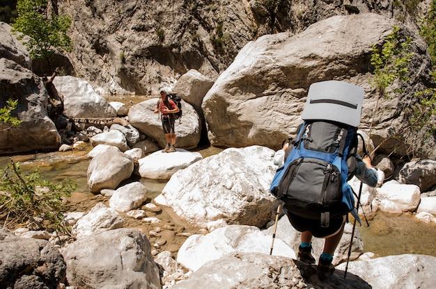 Zwei wanderer, die mit rucksäcken durch schlucht reisen