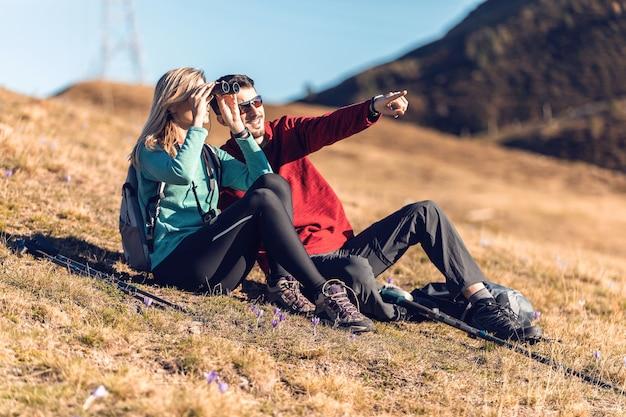 Zwei wanderer genießen die natur, während sie die landschaft mit dem fernglas im berg betrachten.