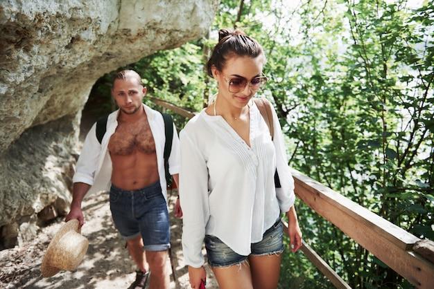 Zwei wanderer mit rucksäcken auf dem rücken in der natur. junge paare mann und frau mögen einen aktiven urlaub mit einem zelt, so dass sie an einem sonnigen tag in die natur gingen