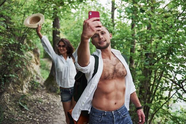 Zwei wanderer mit rucksäcken auf dem rücken in der natur. mann und frau des jungen paares machen selfie-foto-spaziergang an einem sommertag