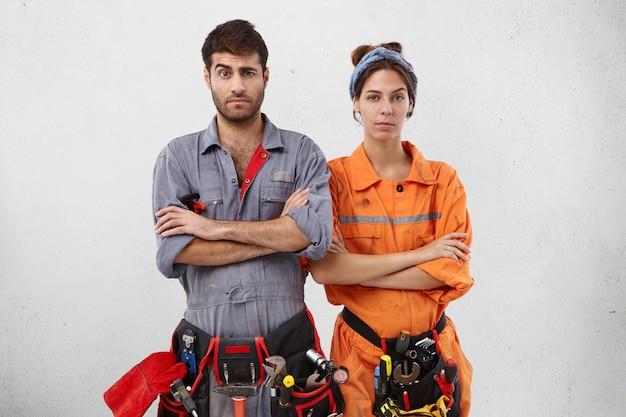 Zwei wartungsarbeiter stehen nebeneinander, halten die hände gefaltet, ziehen verwirrt die augenbrauen hoch,