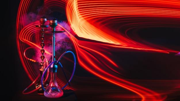 Zwei wasserpfeifen mit shisha-kohlen und rauch mit roter und blauer neonbeleuchtung auf dem tisch auf einem dunklen hintergrund