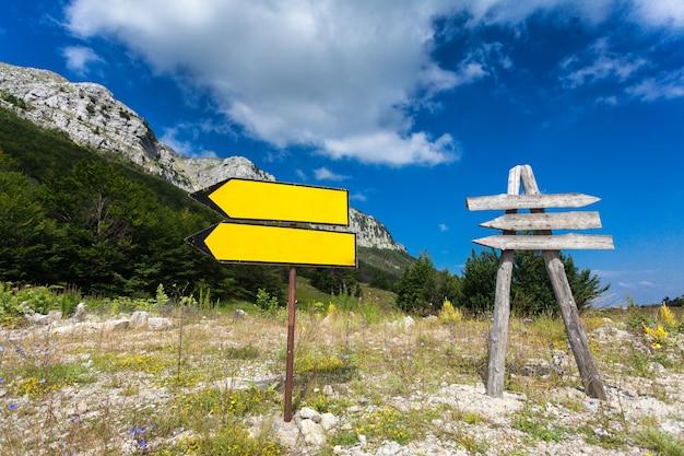 Zwei wegweiser an der kreuzung bei berg und wald