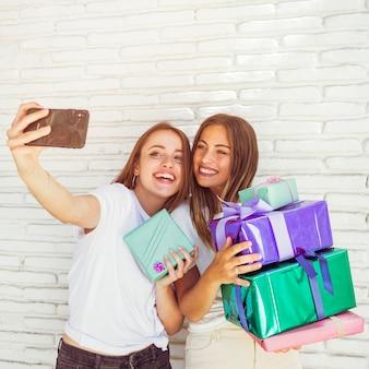 Zwei weibliche beste freunde mit dem geburtstagsgeschenk, das selfie auf mobiltelefon nimmt