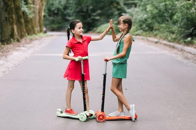 Zwei weibliche freunde, die auf dem roller geben hohe geste fünf auf straße stehen