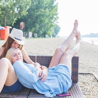 Zwei weibliche freunde, die auf klubsessel am strand sich entspannen
