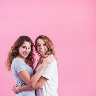 Zwei weibliche freunde, die gegen rosa hintergrund sich umarmen