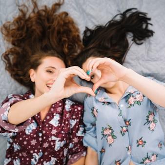 Zwei weibliche freunde, die herzform machen