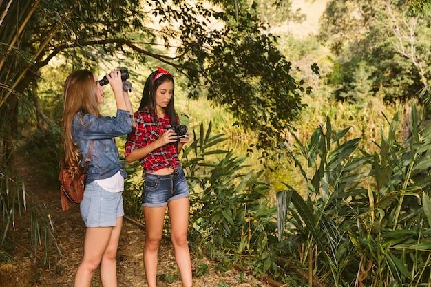 Zwei weibliche freunde, die wald mit ferngläsern und kamera erforschen