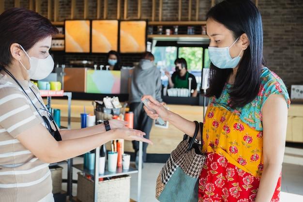 Zwei weibliche freunde mit gesichtsmaske, die ihre hände mit antiseptischem spray im café besprühen