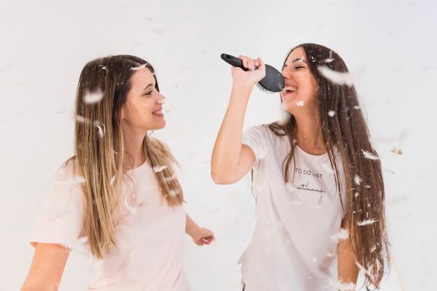 Zwei weibliche freunde singen lied und machen spaß mit federn in der luft