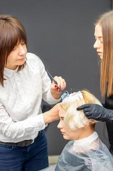 Zwei weibliche friseure, die haare der jungen kaukasischen frau im friseursalon färben