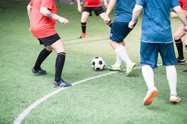 Zwei weibliche fußballmannschaften in roter und blauer sportuniform laufen grünes feld herunter, während ball während des spiels angreifend