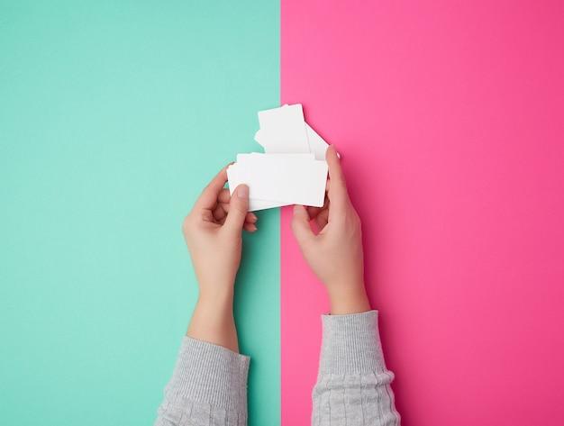 Zwei weibliche hände, die einen stapel leere weiße karten halten