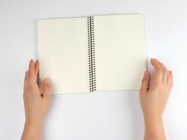 Zwei weibliche hände, die offenen notizblock mit leeren blättern halten