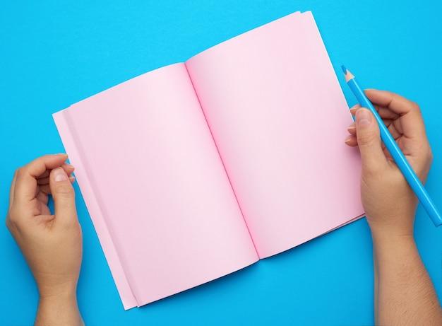 Zwei weibliche hände, die offenen notizblock mit leeren rosa blättern auf einem blauen hintergrund halten
