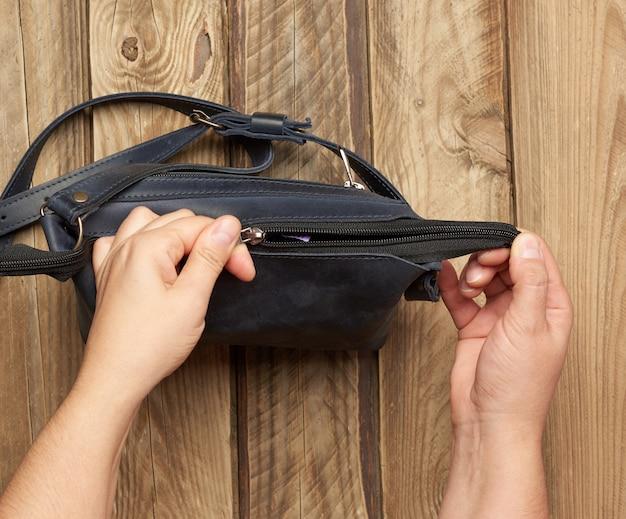 Zwei weibliche hände halten eine blaue ledertasche auf einem grauen holztisch, draufsicht